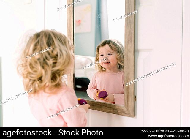 A little girl looking at her reflection in the mirror