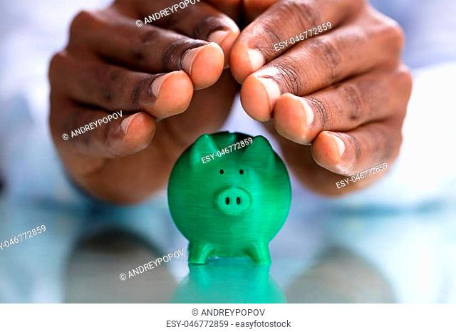 Close-up Of Hand Protecting The Green Miniature Piggybank On Desk