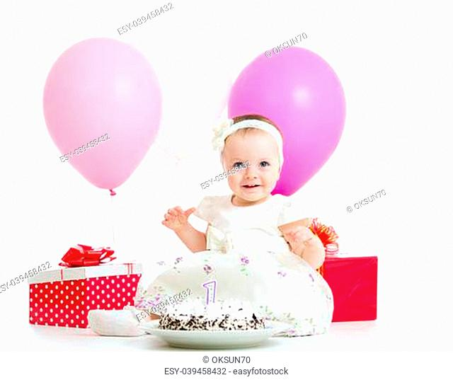 Joyful baby girl with cake, balloons and gifts. Isolated on white