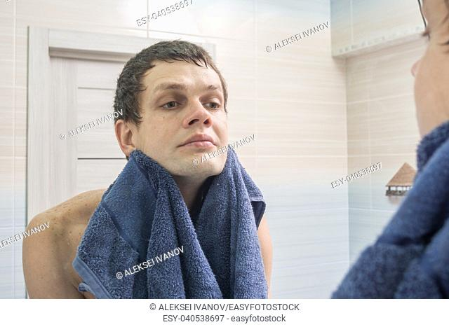 A young man shaved and washed himself wiping himself dry with a towel