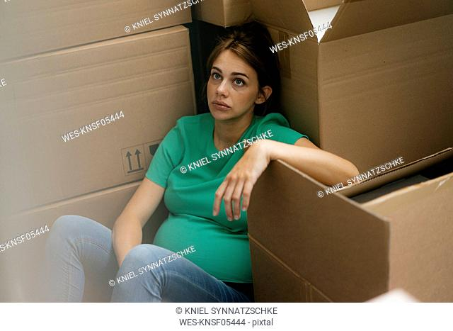 Exhausted pregnant woman sitting on floor surrounded by cardboard boxes