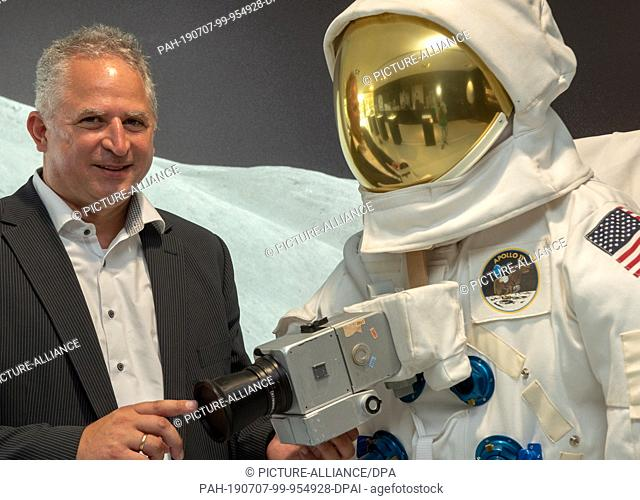 01 July 2019, Baden-Wuerttemberg, Oberkochen: Vladan Blahnik, head of lens development, stands next to a space suit in the Zeiss Museum