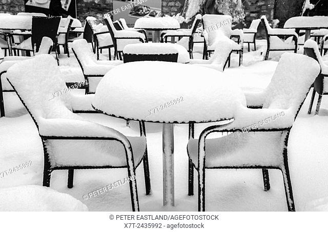 Snow and ice covering cafe chairs and tables in a wintery Gulhane Park, Sultanahmet, Istanbul, Turkey