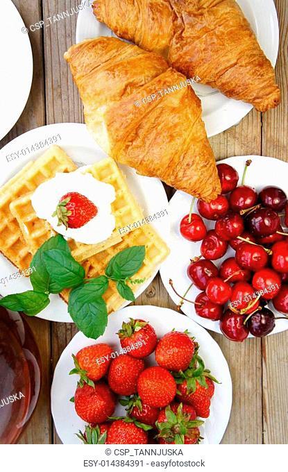 Tasty breakfast - tea, croissants, wafers and fruits