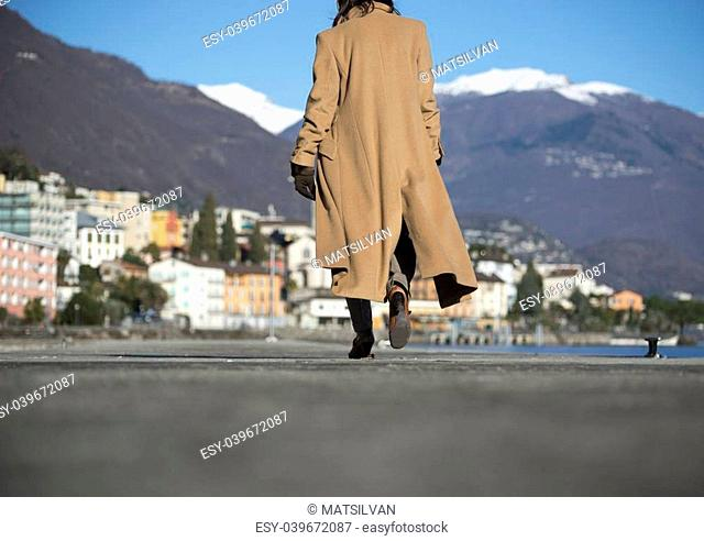 Elegant woman walking on the street and with snow-capped mountain