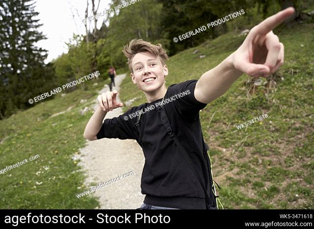 Young boy in countryside, pointing with his finger. Bad Tölz, Upper bavaria, Germany