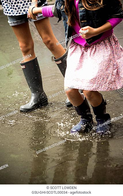 Two Young Girls Walking Through Puddle in Rubber Boots