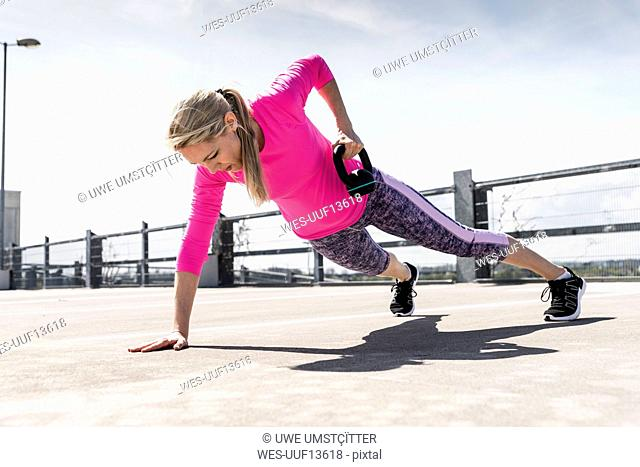Woman training with dumbells, doing one-armed plank