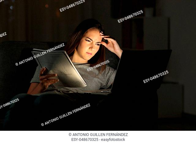 Worried student watching online tutorial in the night sitting on a couch in the living room at home