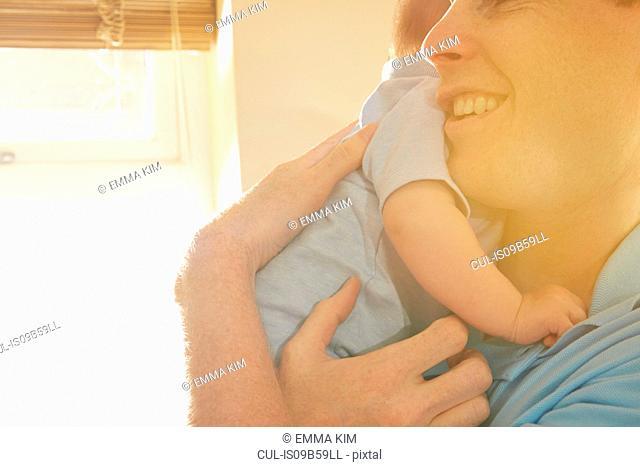 Mature man cradling baby son