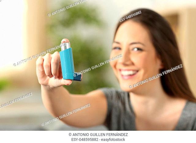 Girl showing an asthma inhaler sitting on a couch in the living room at home