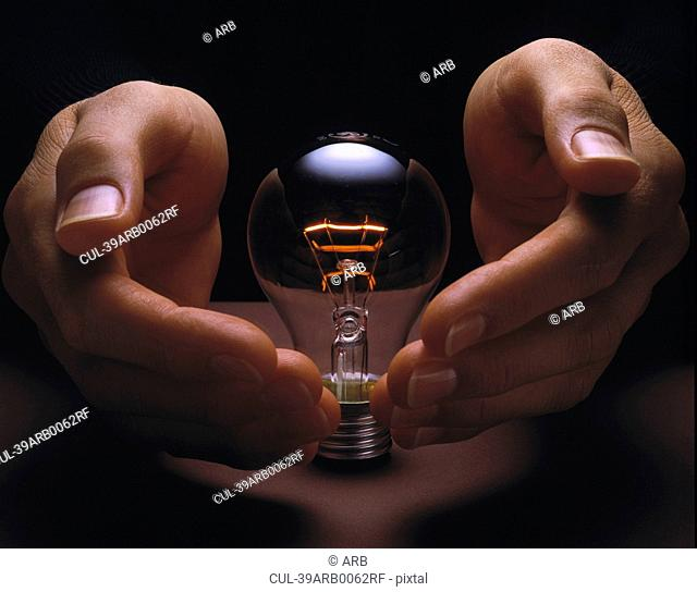 Hands cupping glowing light bulb