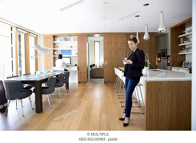 Pregnant businesswoman texting with cell phone in kitchen