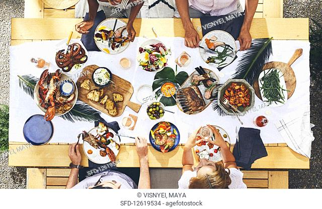 Friends sitting around a table laid with grilled dishes