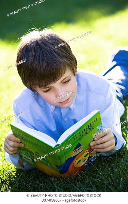 Boy enjoying reading a book in the garden