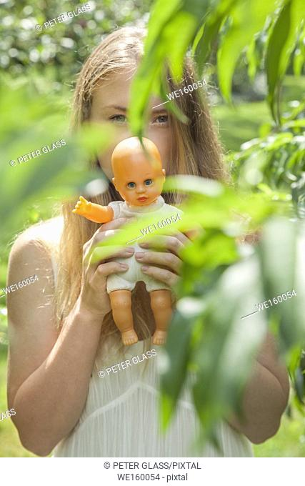 Young woman outdoors, surrounded by leaves, holding a doll