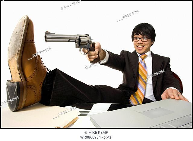Businessman sitting at desk pointing shotgun at foot