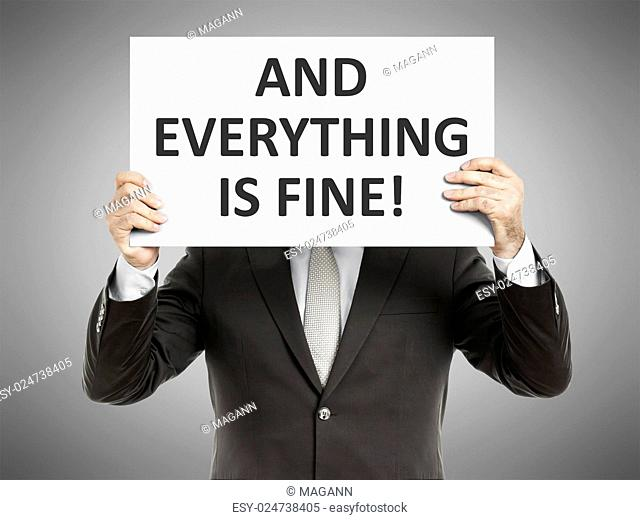 A business man holding a paper in front of his face with the message and everything is fine!