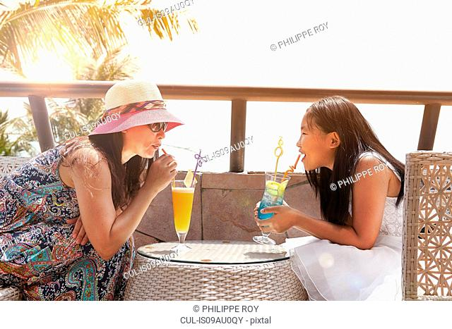 Girl and mother having soft drinks at beach cafe, Zhuhai, Guangdong, China