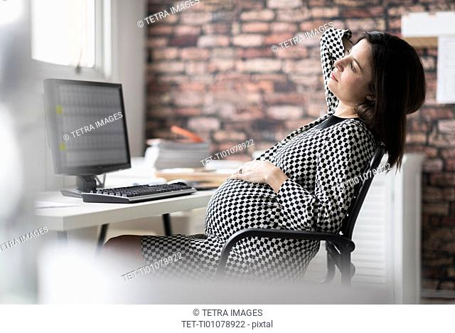 Pregnant woman relaxing in office