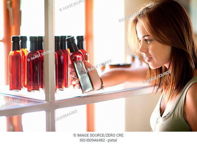 Woman reading vinegar bottle in grocery