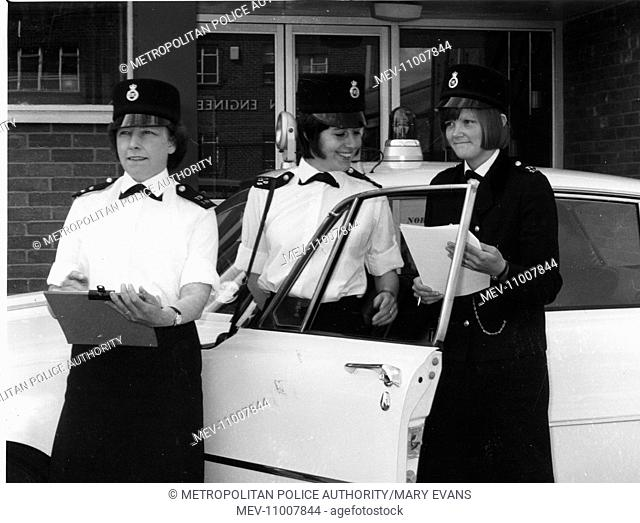 Three women police officers (mobile officers) standing by a car outside a London police station. They are wearing the Norman Hartnell uniform
