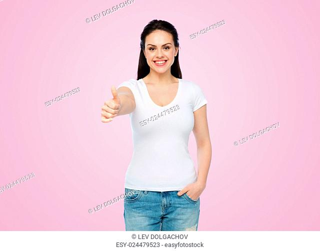 advertisement, gesture, clothing and people concept - happy smiling young woman or teenage girl in white t-shirt showing thumbs up over pink background