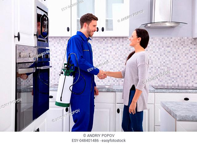 Male Pest Control Worker Shaking Hands With Happy Woman In Kitchen