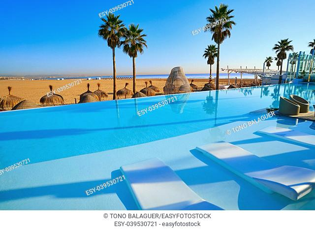 Resort infinity pool in the beach with palm trees paradise