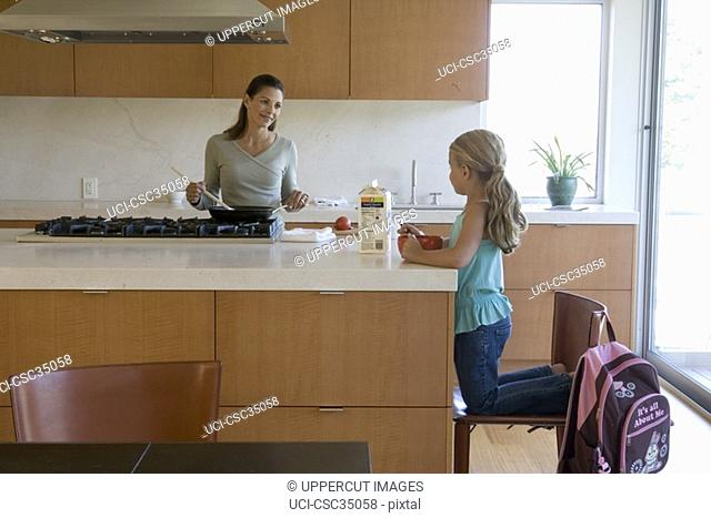 Mother cooking for daughter in kitchen