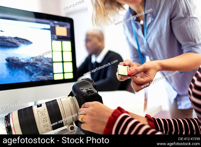 Photography students with digital camera and memory card at computer