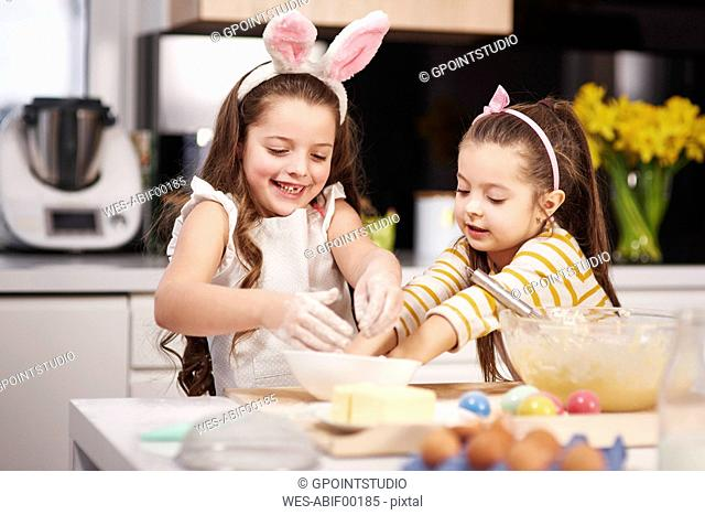 Two sisters having fun baking Easter cookies in kitchen together