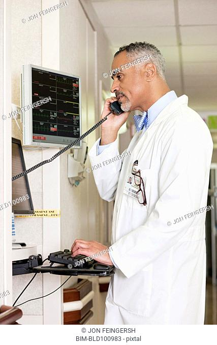 African American doctor talking on telephone in hospital