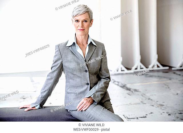 Portrait of mature businesswoman wearing grey pantsuit
