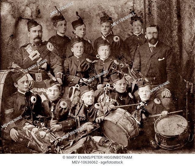 Uniformed members of the boys' pipe band at the Dumfries Industrial School pose with their instruments - bagpipes and drums - accompanied by two adult members...