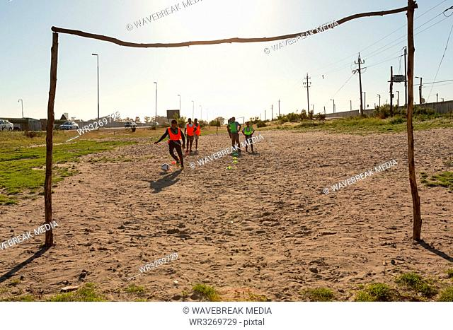 Kids playing football in the ground
