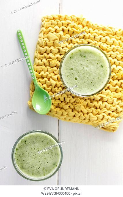 Two glasses of curly cale banana smoothie, yellow potholder and spoon on white wooden table, elevated view