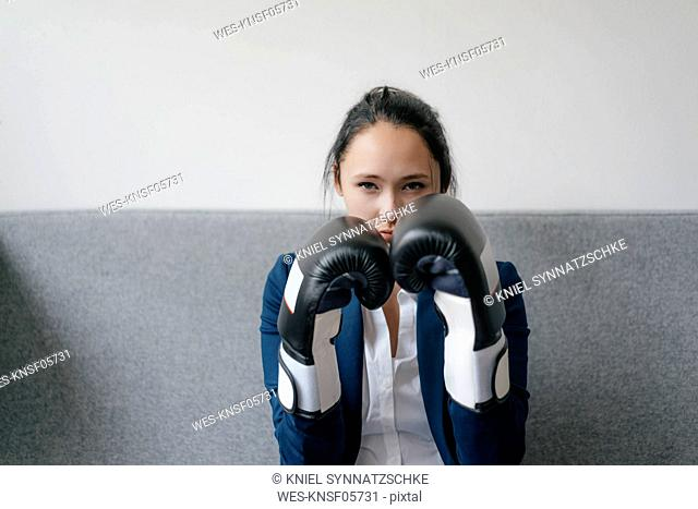 Portrait of young woman on couch wearing boxing gloves