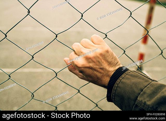 Male hand on chainlink fence