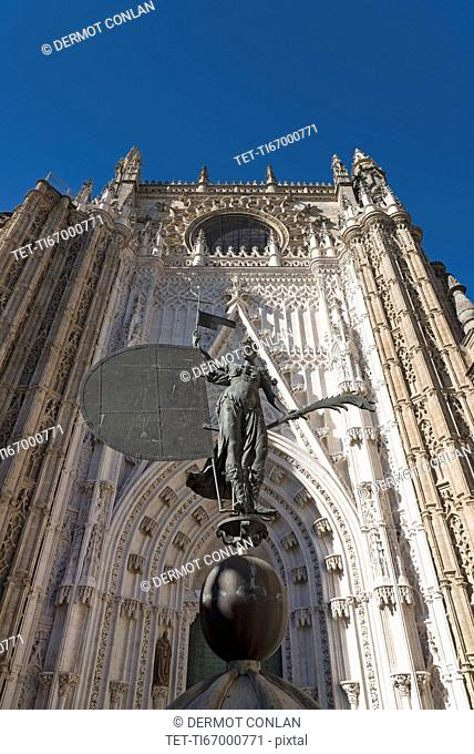 Spain, Andalusia, Seville, Giralda Tower with sculpture presenting faith in foreground