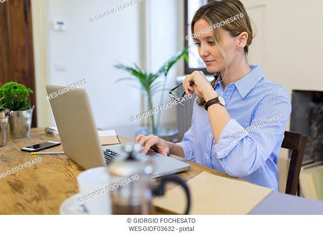 Woman using laptop on wooden desk at home