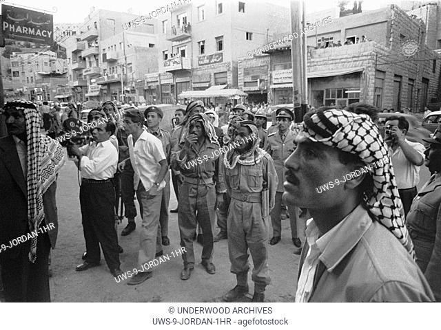 Amman, Jordan: July, 1958.Men and soldiers gathered on a street intently watching something in a storefront window, possibly news reports of the overthrow of...
