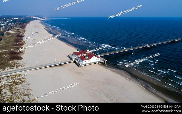 28 March 2020, Mecklenburg-Western Pomerania, Ahlbeck: The long beach, the beach promenade and the pier in the Baltic resort of Ahlbeck (aerial photo with a...