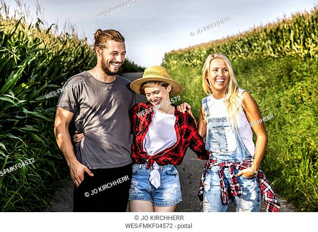 Happy friends on country lane at a cornfield