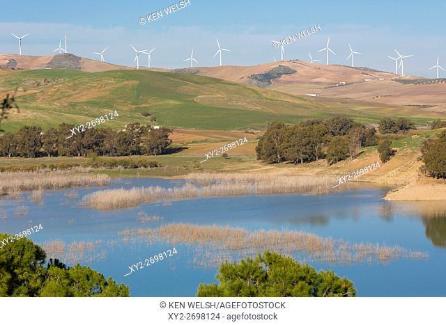 View across Guadalhorce dam, Malaga Province, Andalusia, Spain, to farmland and wind turbines beyond. Embalse de Conde de Guadalorce