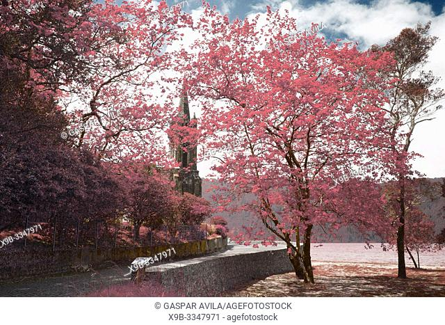 Simulated infrared photo of trees and gothic style chapel on the shore of Furnas lake. Sao Miguel, Azores islands, Portugal