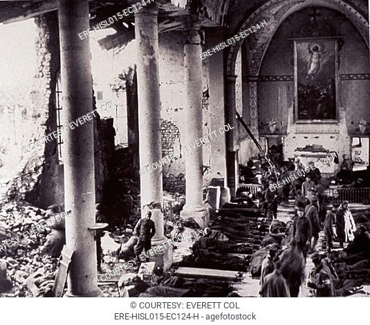 A first aid station in a bombed-out church, on the western front in World War I. U.S. soldiers lay on stretchers on the floor