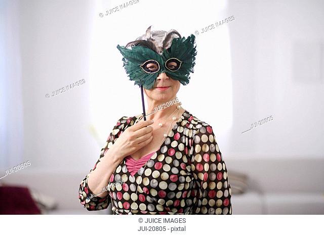 Portrait of senior woman wearing masquerade mask