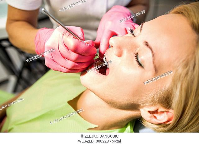 Orthodontist adjusting braces