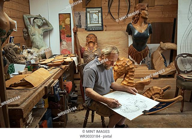 A craftsman, woodworker seated on a stool in a workshop working on a drawing, sketching using charcoal. Surrounded by wooden carved and painted female ship's...